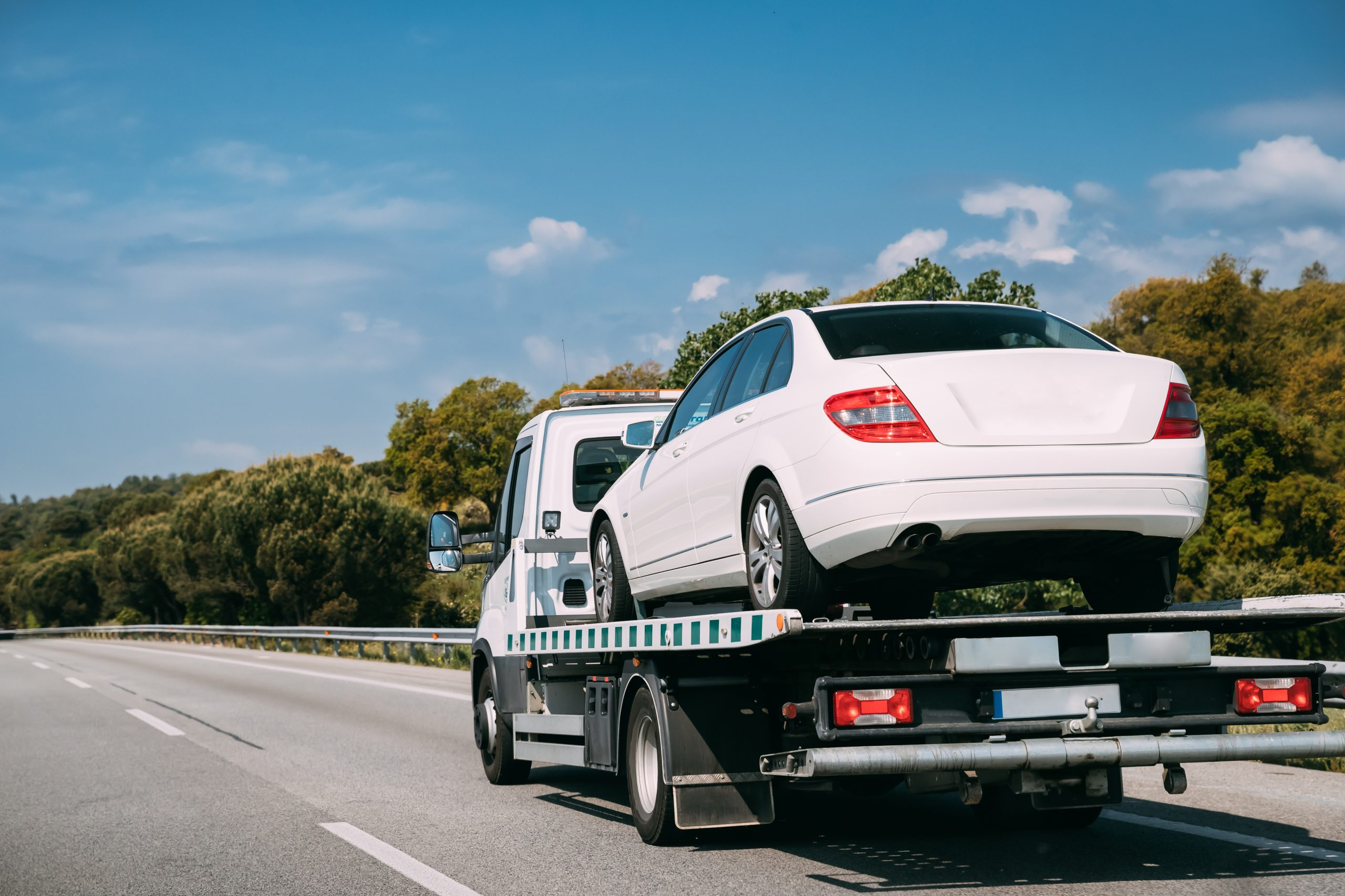 Tow truck transporting white car